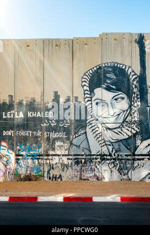 View of graffiti commemorating Leila Khaled on Israeli West Bank Barrier separation wall, Bethlehem, West Bank, Palestine - Stock Photo
