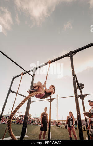 People watching female athlete climbing rope - Stock Photo