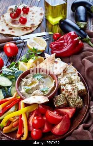 Delicious vegetarian baba ganoush with fresh vegetables, cheese, pita bread and ingredients on the wooden table: eggplants, red bell pepper, olive oil - Stock Photo