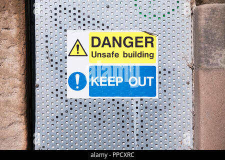 Danger unstable building keep out sign on door entrance - Stock Photo