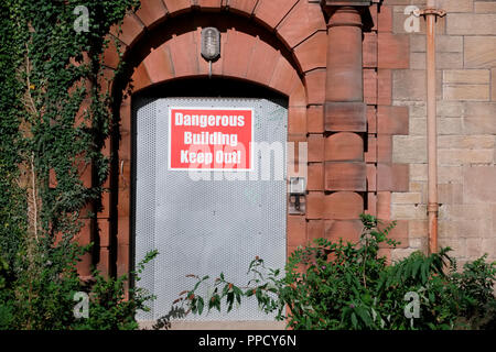 Dangerous building unstable keep out sign on entrance door - Stock Photo
