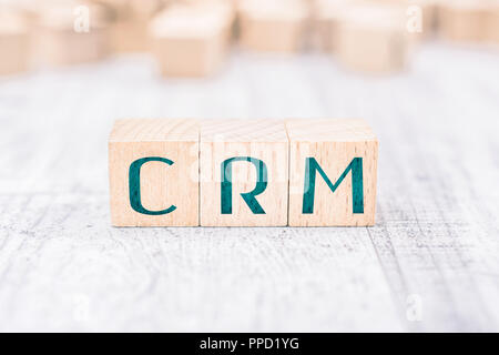 The Abbreviation CRM Formed By Wooden Blocks On A White Table - Stock Photo