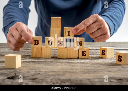 Close up of the hands of a man building the word Business with wooden blocks on a rustic table in a conceptual image. - Stock Photo