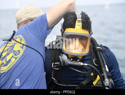 CARTAGENA, Colombia (Sept. 4, 2018) - Navy Diver 1st Class Jason Andritsch, left, and Navy Diver 1st Class Enrique Escoto, prepare for diving operations by conducting physical checks to Escoto's gear prior to jumping into the water during UNITAS LIX. The annual international maritime exercise focuses on strengthening regional partnerships and encourages establishing new relationships through the exchange of maritime mission-focused knowledge and expertise during multinational training operations. - Stock Photo