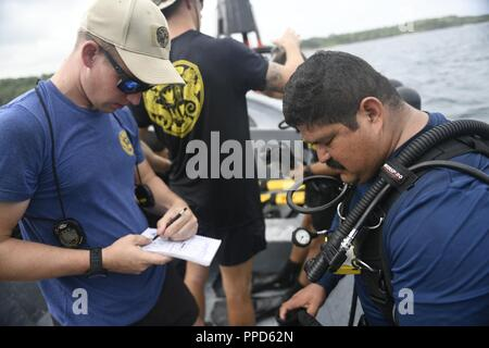 CARTAGENA, Colombia (Sept. 4, 2018) - Navy Diver 1st Class Jason Andritsch, left, and Navy Diver 1st Class Enrique Escoto, prepare for diving operations by reviewing mandatory checklists AND Escoto's equipment prior to jumping into the water during exercise UNITAS LIX. The annual international maritime exercise focuses on strengthening regional partnerships and encourages establishing new relationships through the exchange of maritime mission-focused knowledge and expertise during multinational training operations. - Stock Photo