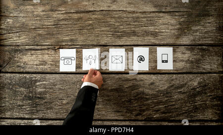 High angle view of businessman laying out white cards with communication and people icons on a rustic wooden background. - Stock Photo