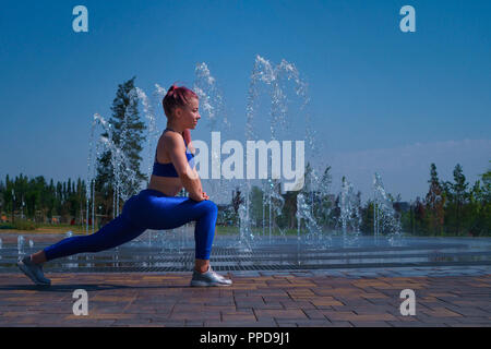 Girl on street workout. Slender young woman makes wide steps. She is dressed in sport top and leggins. Healthy lifestyle. - Stock Photo