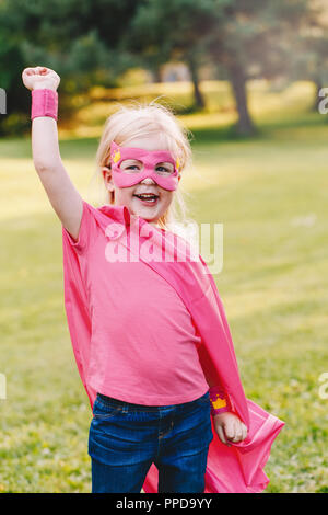 Cute adorable preschool Caucasian child playing superhero in costume. Girl kid wearing pink mask and cape having fun outdoors in park. Happy active ch - Stock Photo