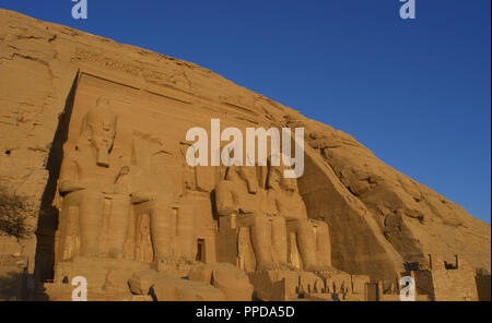Egyptian art. Great Temple of Ramses II. Four colossal statues depicting the pharaoh Ramses II (1290-1224 BC) seated with the nemes head and surmounted by the double crown. 19th Dynasty. New Kingdom.  Abu Simbel. Egypt. - Stock Photo