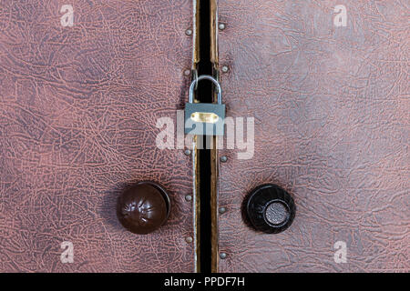 Locked padlock on old vintage door with round plastic door handle - Stock Photo