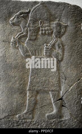 Hittite art. Orthostat. 8th century BC. Relief: Man carrying a gazelle.  Found in old city of Sma'al /Zincirli (Turkey). 775 BC. Pergamon Museum. Museum Island. Berlin. Germany. - Stock Photo