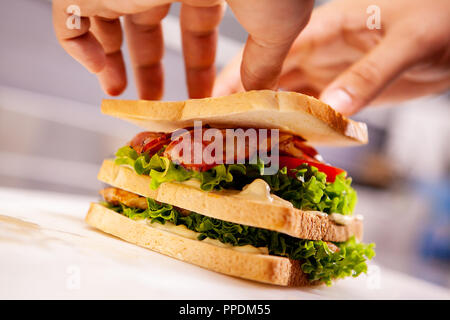 Chef making sandwich in rustic style with bacon and fresh vegetables.Delicious food - Stock Photo