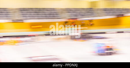 Abstract sporting background image cyclists in velodrome cycling in group around wooden track. - Stock Photo