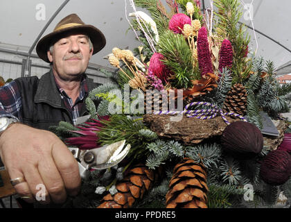 Johann Raab from the family business 'Blumen und Grabpflege Franziska Raab' from Perlach makes a floral arrangement as grave decoration for All Saints' Day. - Stock Photo