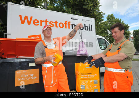 The Wertstoffmobil (recycling truck) of the Waste Management Corporation Munich (AWM) on the Platz der Freiheit in Neuhausen. Fortnightly the citizens of Munich can bring their recyclables here. The photo shows two AWM employees with a recycling bin for small electrical appliances. - Stock Photo