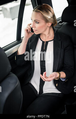 Businesswoman talking on cellphone while travelling in car - Stock Photo