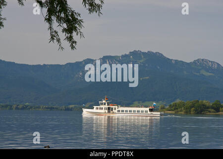 Boat trip on the Chiemsee (Chiemgau, Upper Bavaria, Germany) with the Chiemgau Mountains and the Kampenwand in the background. - Stock Photo