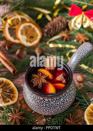 Christmas mulled wine with cinnamon, orange and star anise in a ceramic bowl with winter decorations. - Stock Photo