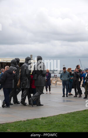 Tourists having their photo taken in front of The Beatles statue at the Pier Head Liverpool UK. - Stock Photo