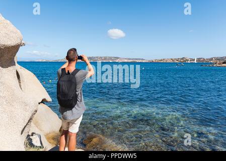 young caucasian man taking a photo of the coast of the Mediterranean sea in Sardinia, Italy, highlighting La Maddalena, Santo Stefano and Caprera isla - Stock Photo