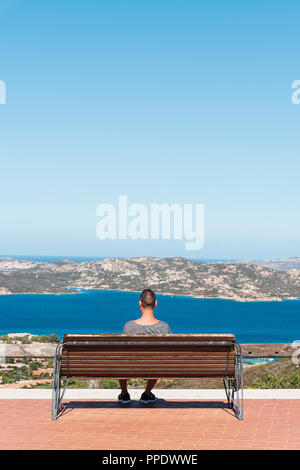 young caucasian man, seen from behind, sitting in a bench in Palau, at the Northern coast of Sardinia, Italy, observing the Mediterranean sea and La M - Stock Photo