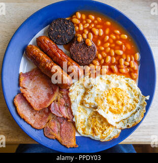 overhead view of a full english fried breakfast of eggs bacon beans and sausages on a café table. - Stock Photo