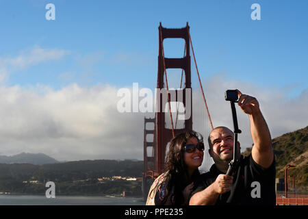 A young couple on vacation in San Francisco, California take a 'selfie' photograph with a GoPro camera - Stock Photo