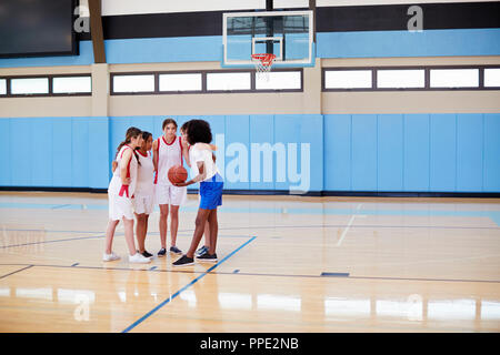 Female High School Basketball Players In Huddle Having Team Talk With Coach - Stock Photo