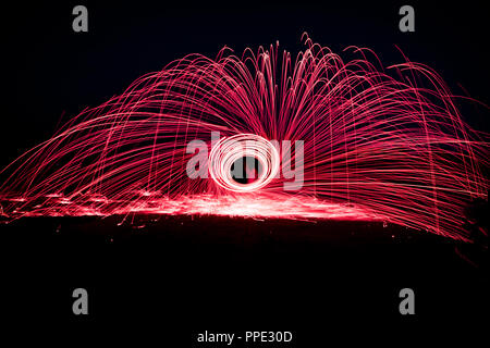 Light Painting with spinning steel wool, creating gorgeous circular streaks of purple light from burning steel wool inside a whisk attached to a rope. - Stock Photo