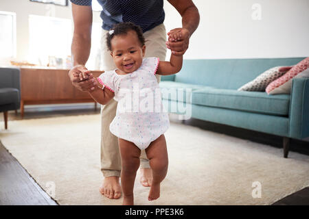 Father Encouraging Baby Daughter To Take First Steps At Home - Stock Photo