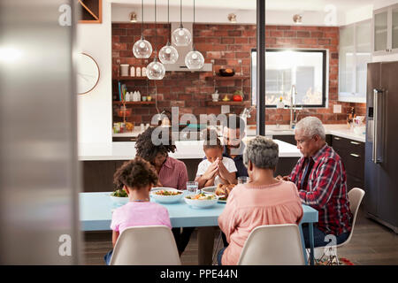 Multi Generation Family Praying Before Meal Around Table At Home - Stock Photo