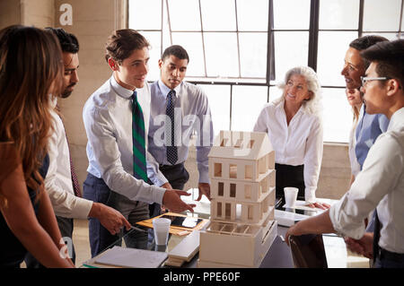 Architects discussing the scale model of a building - Stock Photo