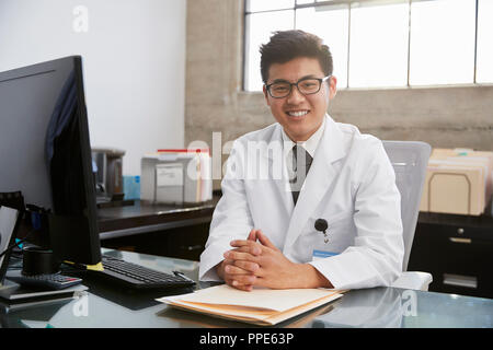 Young Asian male doctor sitting at desk, portrait - Stock Photo