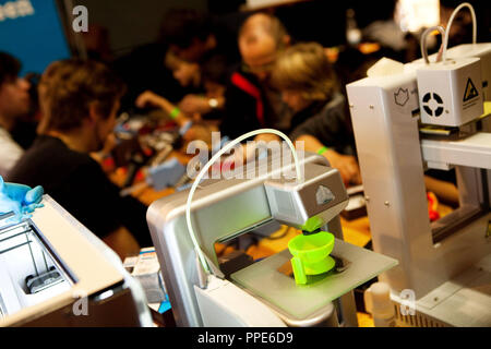 3-D printer at the Elektro Conrad stand at the maker fair 'Make Munich' in the Tonhalle of the Kultfabrik. It heats plastic and prints it in many layers on top of each other. Here is a green cup. - Stock Photo