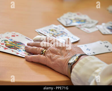 Older people playing a card game together in the community center of the sheltered accommodation of Diakonie Hasenbergl on Schleissheimer Strasse. In particular poor and lonely seniors are to be integrated again into a life worth living. - Stock Photo
