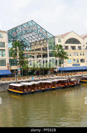 The Riverside Point Shopping Mall with Shops Bars and Restaurants  near Clarke Quay in Downtown Singapore with Taxi Boats on Singapore River - Stock Photo