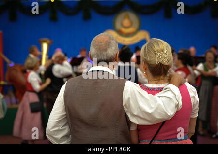 An elderly couple listening to the concert 'Die Hoerbacher Rassoraeuber treffen das Hattenhofer Blech' in the 'Herzkasperl' festival tent on the Oidn Wiesn (Old Wiesn). - Stock Photo