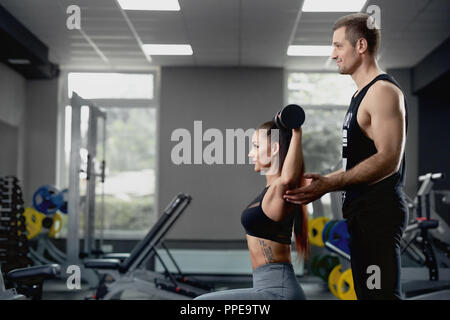 Side view of handsome male personal trainer helping muscular woman working with heavy dumbbells at gym. Young man motivating beautiful client to properly performing exercises to keep her body in tone. - Stock Photo