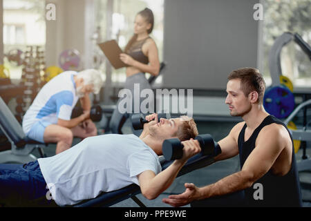 Young cheerful personal coach helping perform to muscular guy doing exercises lying with dumbbells in dark gym. On blurry background, hot girl, personal trainer, supporting senior gray man. - Stock Photo
