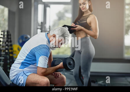 Young hot female personal trainer supporting senior gray man to properly performing exercises to keep his body in tone. Elderly man doing exercise with dumbbell, while coach standing near at gym. - Stock Photo