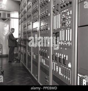 1950s, man checking on the operation of wireless broadcasting equipment or monitors, England, UK. - Stock Photo