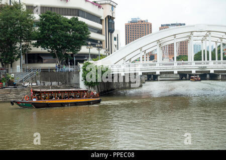 The Elgin Bridge River Crossing with Tourist Taxi Boat on the Singapore River with the Riverwalk Condominium Building in Singapore Asia - Stock Photo