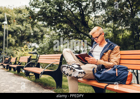 College student with backpack reading book walking in autumn park sitting on bench. Man studying outdoors - Stock Photo