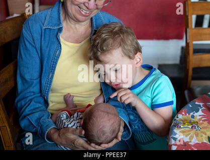 Wheat Ridge, Colorado - Adam Hjermstad Jr., 4, examines his newborn brother, Hendrix, held by their grandmother, Susan Newell, 69. - Stock Photo