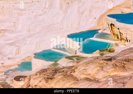 The enchanting pools of Pamukkale in Turkey. Pamukkale contains hot springs and travertines, terraces of carbonate minerals left by the flowing water. - Stock Photo