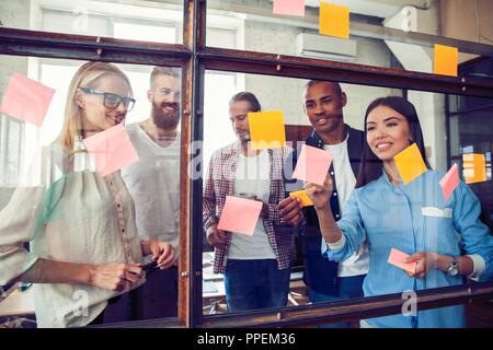 Business people meeting at office and use post it notes to share idea. Brainstorming concept. Sticky note on glass wall - Stock Photo