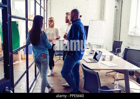 Working as one team. Full length of young modern people in smart casual wear having a meeting while standing behind the glass wall in the creative office. - Stock Photo