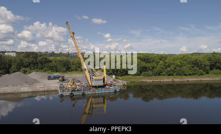 Aerial view large crane an excavator mounted on barge. Excavator on river for unloading and loading sand and rubble. - Stock Photo