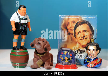 A collection of famous figures of Munich as souvenirs - Franz Josef Strauss in leather pants standing on a beer barrel, Dachshund Waldi, Snow Globe from Oktoberfest, a DVD 'Monaco Franze,' and the bust of Ludwig II as a bauble. - Stock Photo