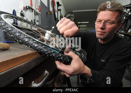 Manager Reiner Lakomiak mounts lucky spikes on a bicycle tire in the workshop of Fahrradzentrale Kropfhamer in the Humboldstrasse. - Stock Photo